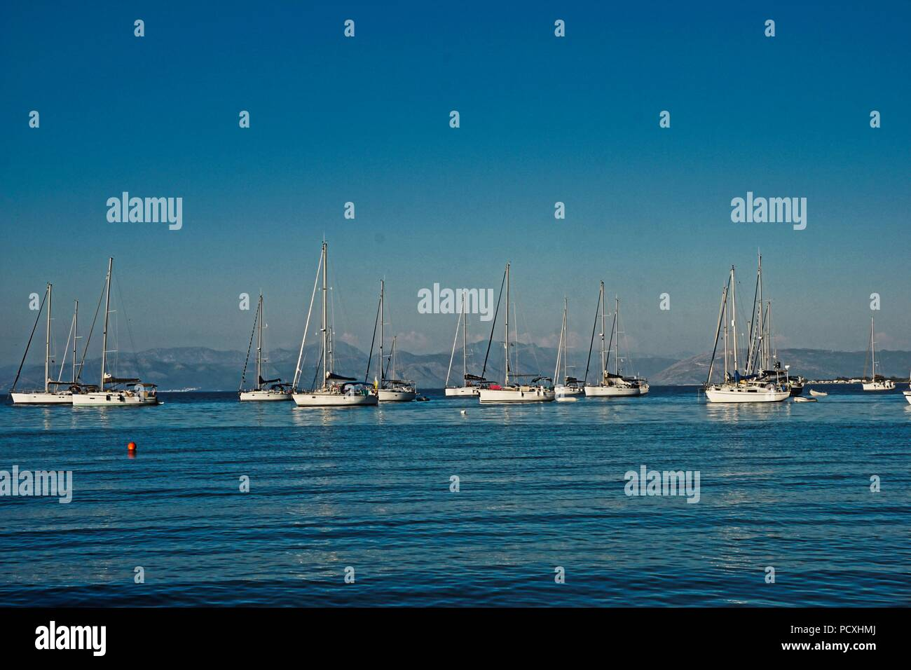 Sailing yachts at anchor in the Greek Islands - Stock Image