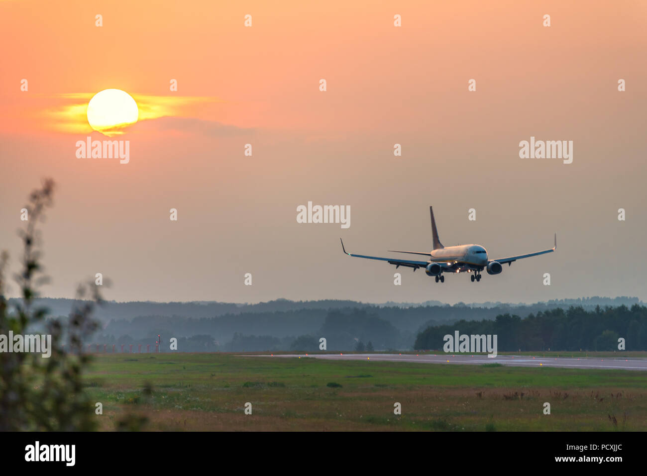 A plane approaches the airport during sunset. - Stock Image
