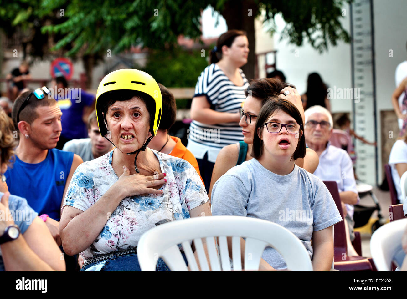 A woman with learning difficulties and a woman with down syndrome sat in main square during the summer festivities, Cherta, Tarragona. - Stock Image