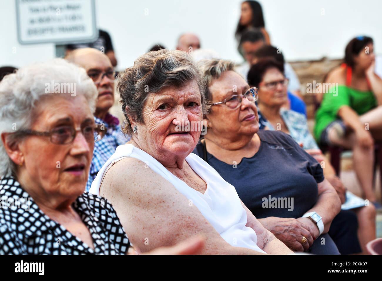 Locals sat in the main square, Cherta, Tarragona, Spain. - Stock Image