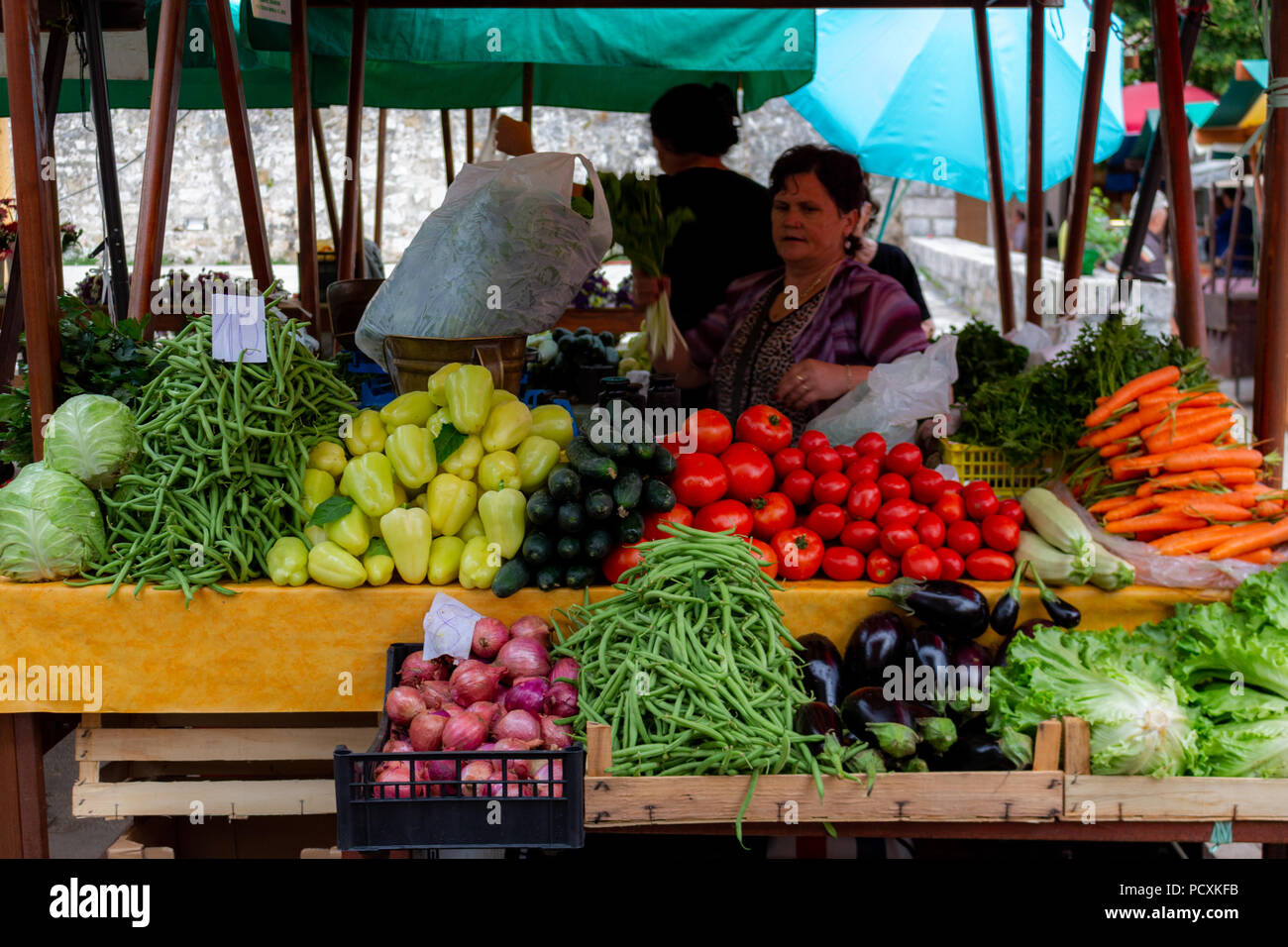 Zadar, Croatia - July 23, 2018: Senior lady selling fruits a vegetables in the market of Zadar old town - Stock Image