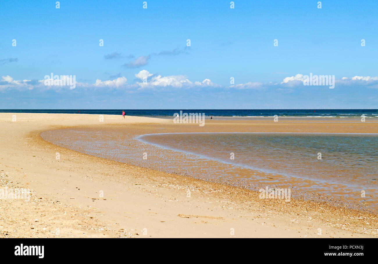 A view of a sparsely populated beach on the North Norfolk coast at Burnham Overy Staithe, Norfolk, England, United Kingdom, Europe. - Stock Image