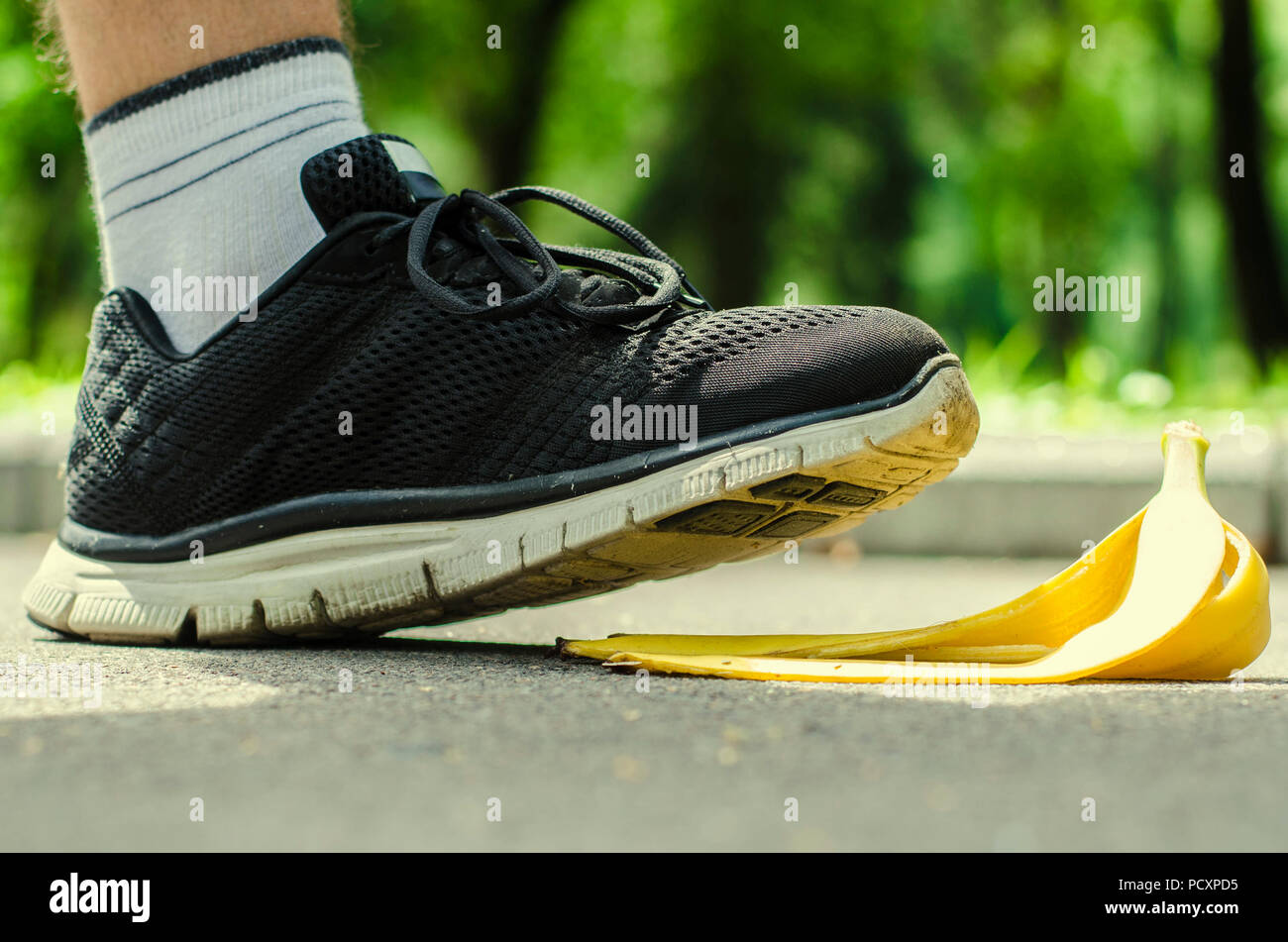 Men's foot in saturated black trainers slides on a yellow peel from banana on the background of summer park. Stock Photo