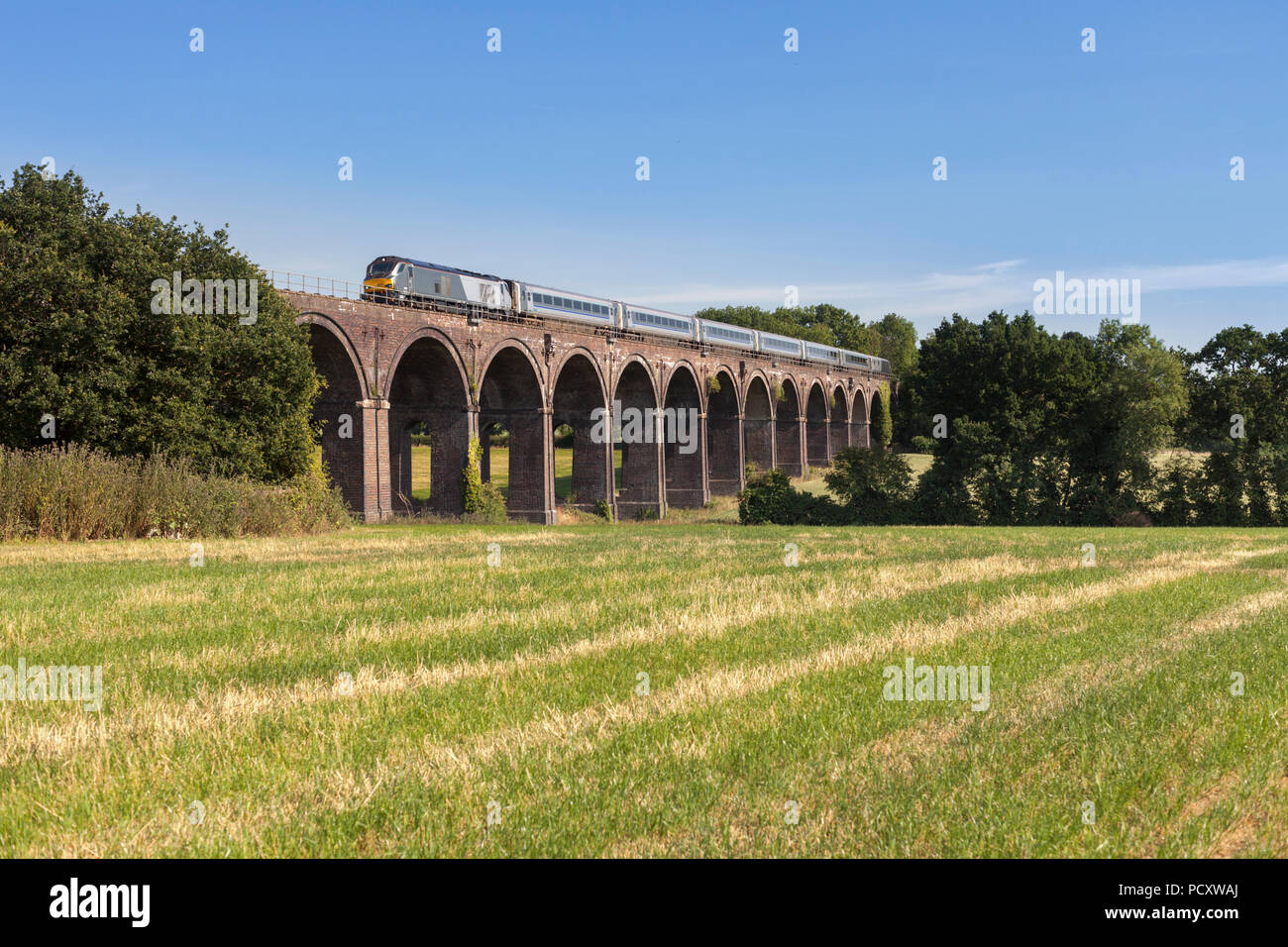 A Chiltern railways class 68 locomotive crossing  Saunderton Viaduct (south of Banbury) with a mainline express train from marylebone - Stock Image