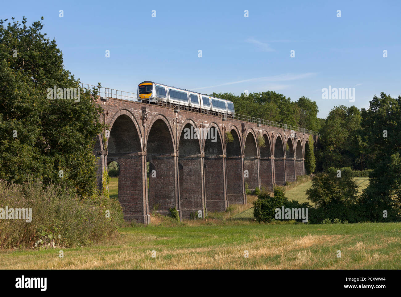 A Chiltern railways class 168 turbostar train crossing  Saunderton Viaduct (south of Banbury)	 with a London to Birmingham Snow hill express - Stock Image