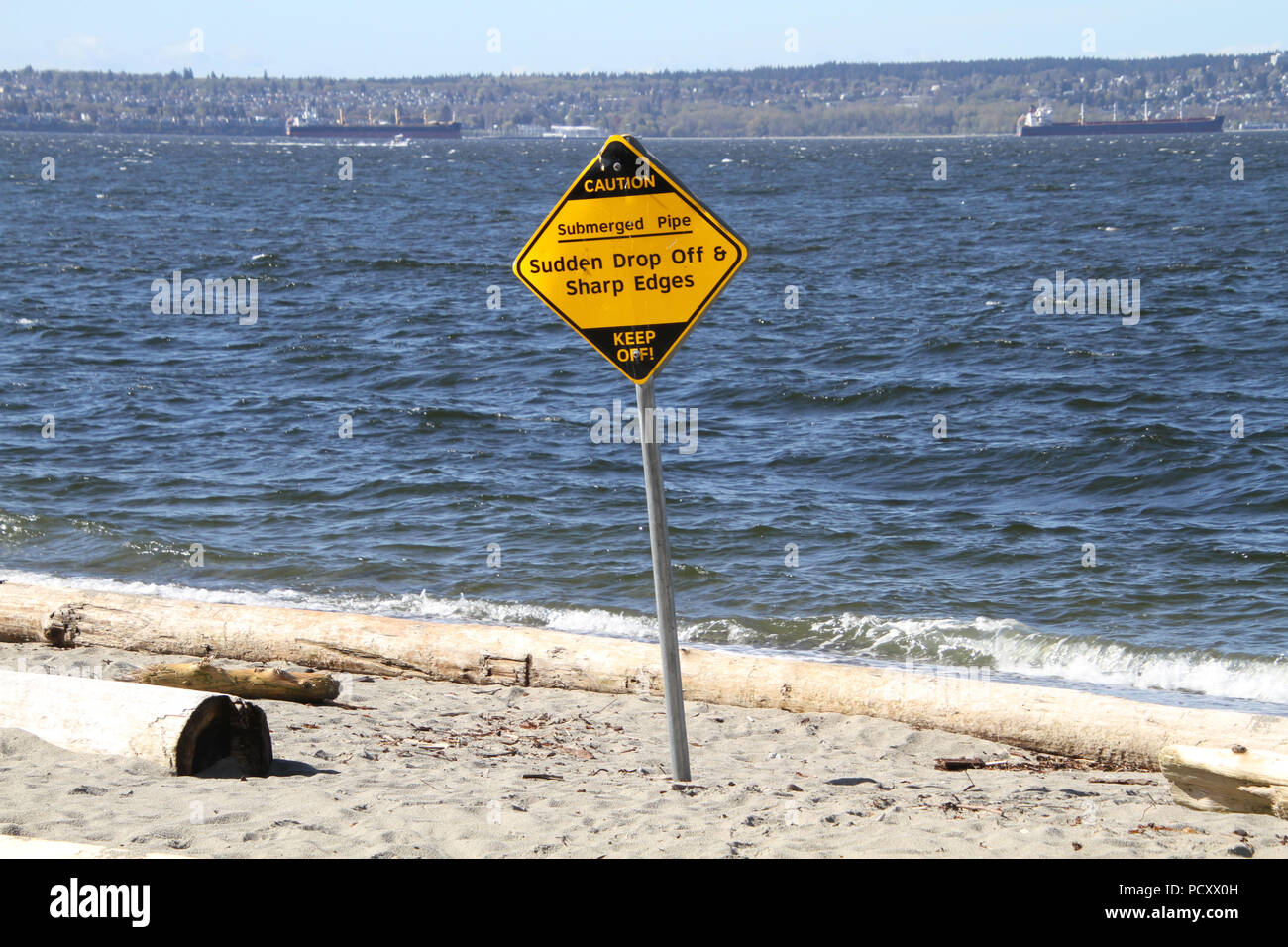 A yellow and black sign indicating a submerged pipe and a drop off with sharp edges on a post in the middle of a sandy beach. - Stock Image