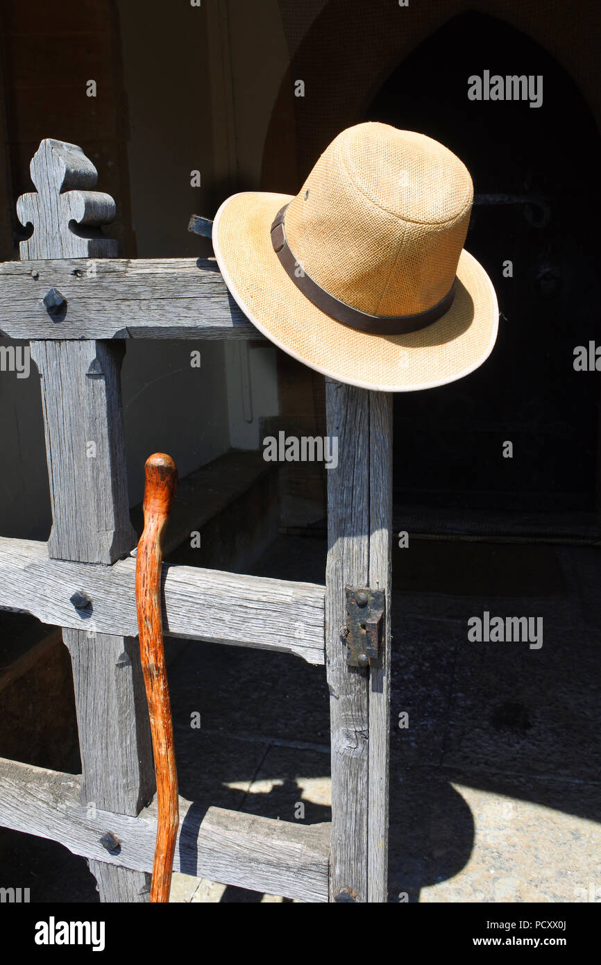 A mans panama hat and walking stick left at the entrance to an English church - John Gollop - Stock Image