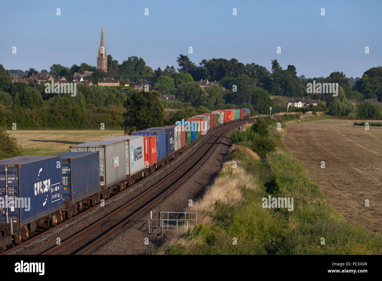 A GB Railfreight intermodal train passes Kings Sutton (South of Banbury) loaded with shipping containers heading to Southampton - Stock Image