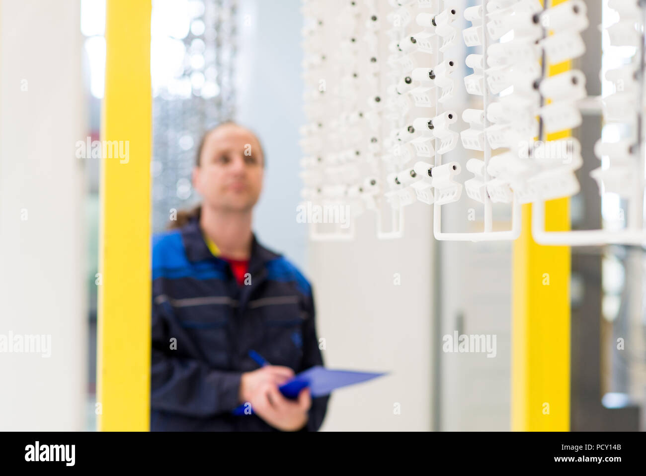 Factory worker checking products on production line. Worker taking notes during quality control of products - Stock Image