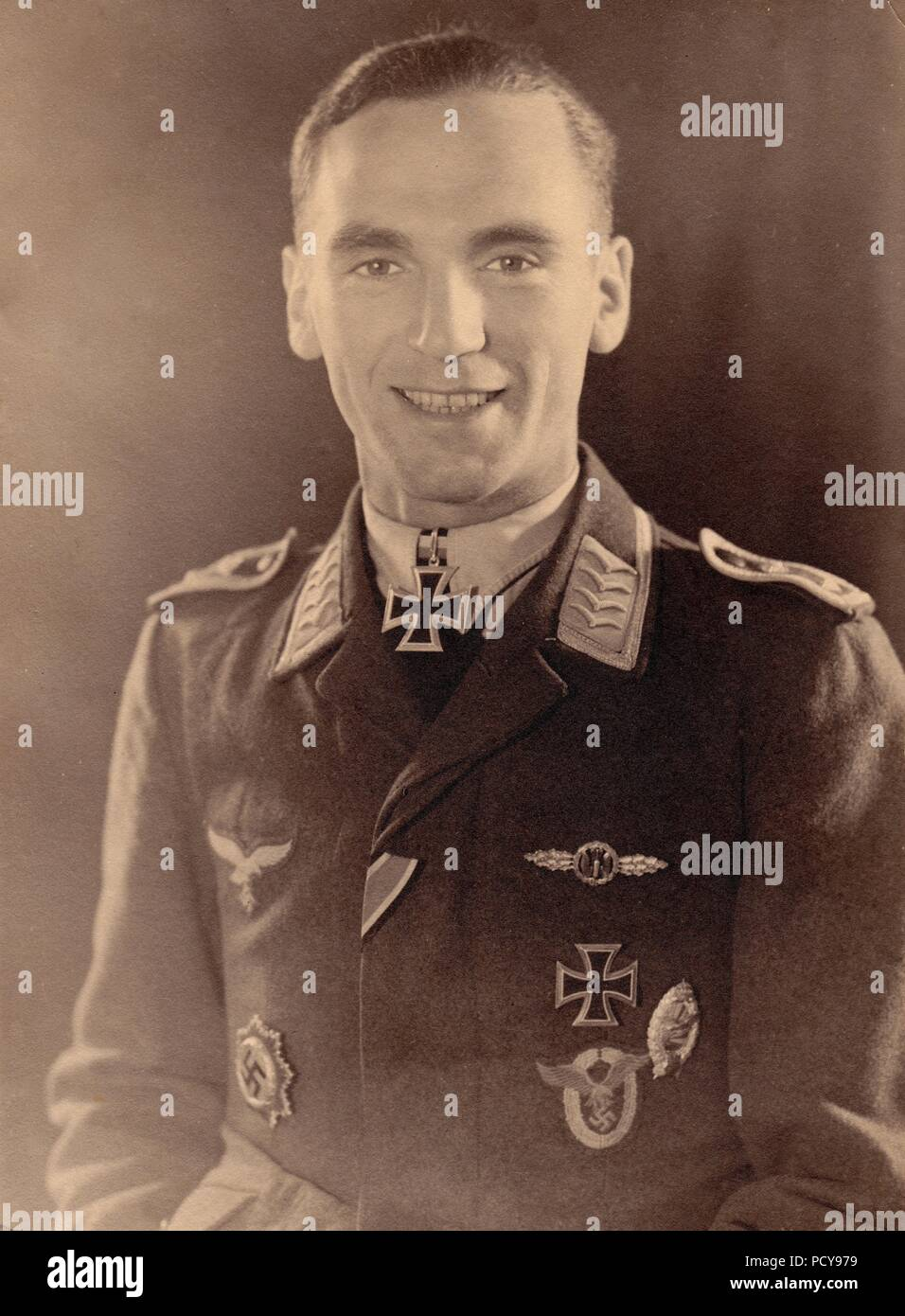 Portrait photograph of Oberfeldwebel Karl Müller, a bomber pilot with 1. Staffel, Kampfgeschwader 2, following his award of the Knight's Cross of the Iron Cross on 15th October 1942. In addition to the Knight's Cross, Müller also wears the German Cross in Gold, Bomber Clasp in Gold, Iron Cross 1st Class, Luftwaffe Pilot Badge in cloth and Bulgarian Pilot Badge. Stock Photo