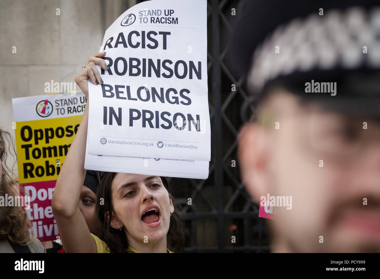 Stand Up To Racism demonstration counter-protest 'Free Tommy Robinson' supporters outside the Royal Courts of Justice in London, UK. - Stock Image