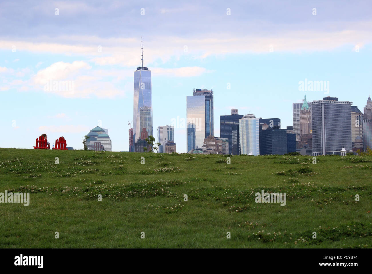 Couple sitting on two red garden chairs on Governors Island Hills watching Financial District skyline, Governors Island on JULY 4th, 2017 in New York, Stock Photo