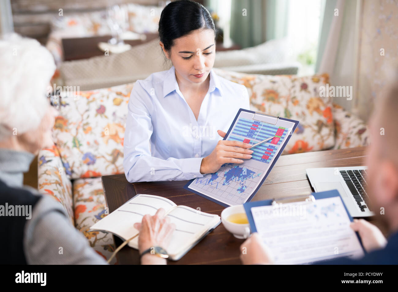 Presentation during a meeting at cafe - Stock Image