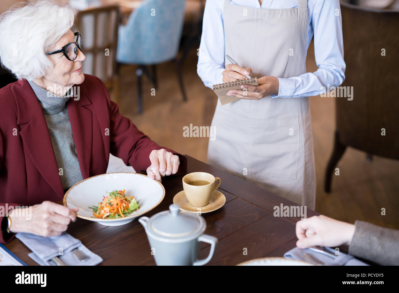 Senior woman at restaurant - Stock Image