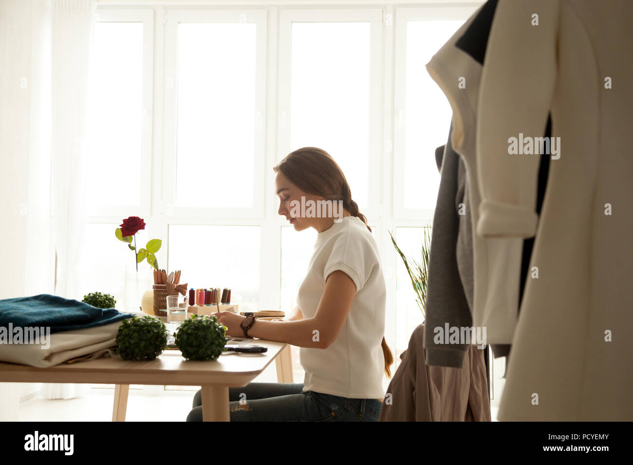 Serious fashion designer creating new collection in her studio - Stock Image