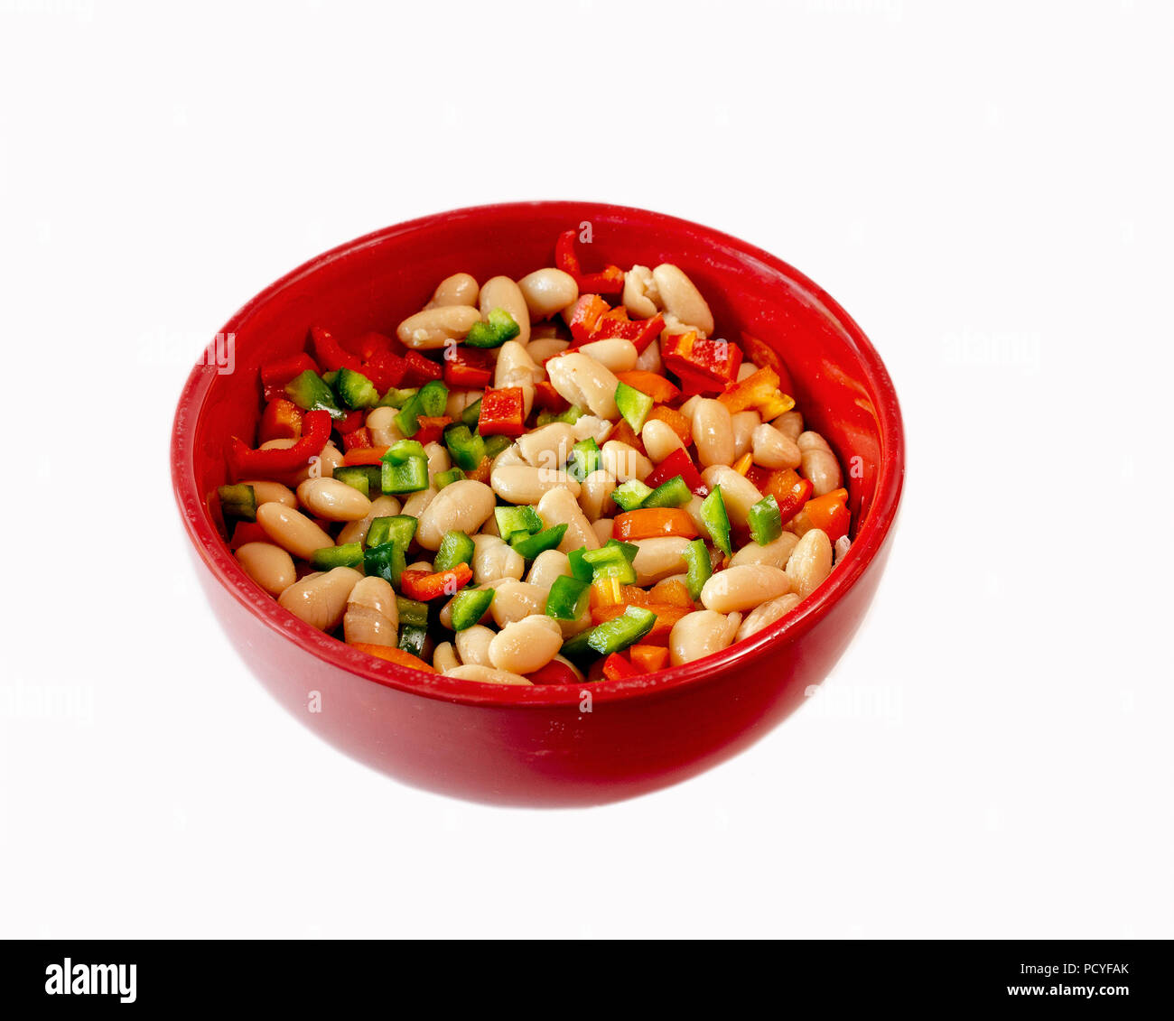 Navy Beans with red, green and orange bell peppers in red bowl isolated on white background -healthy food concept - Stock Image