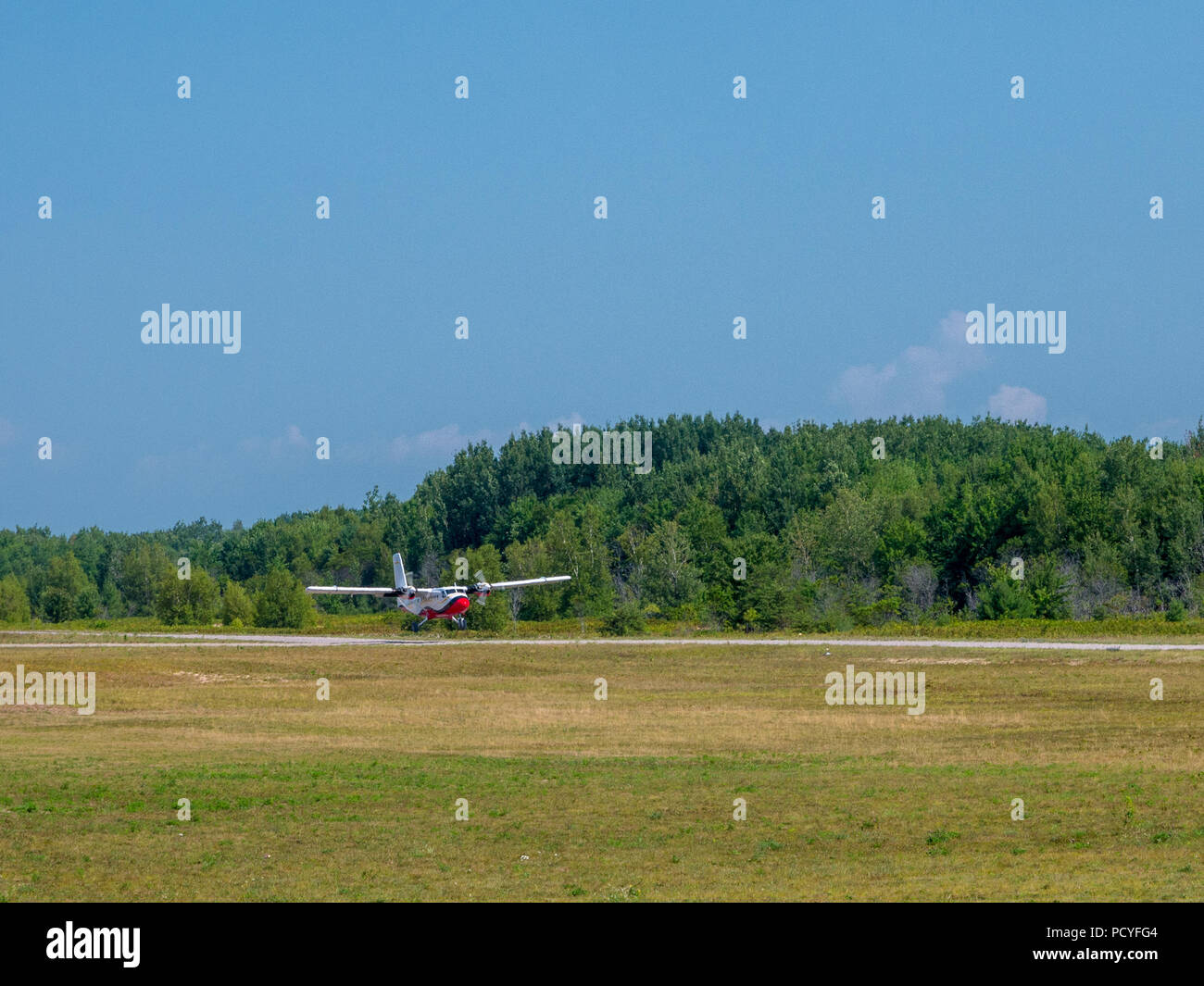 Light private plane is landing on a small airfield on a sunny summer day. - Stock Image