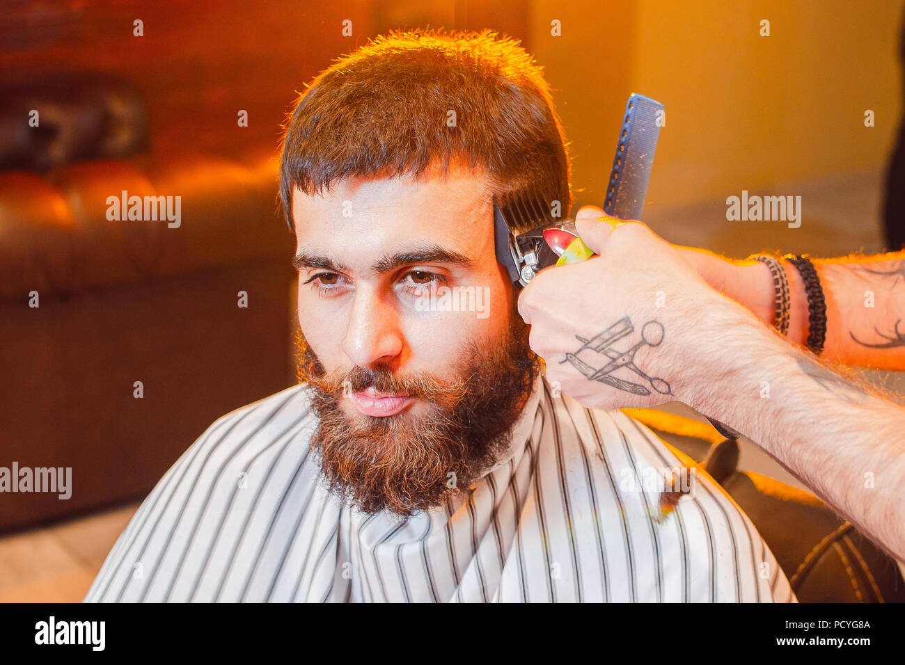 Barber does a haircut on his head with a trimmer to a young handsome guy with a mustache and beard. Men's hair salon. - Stock Image