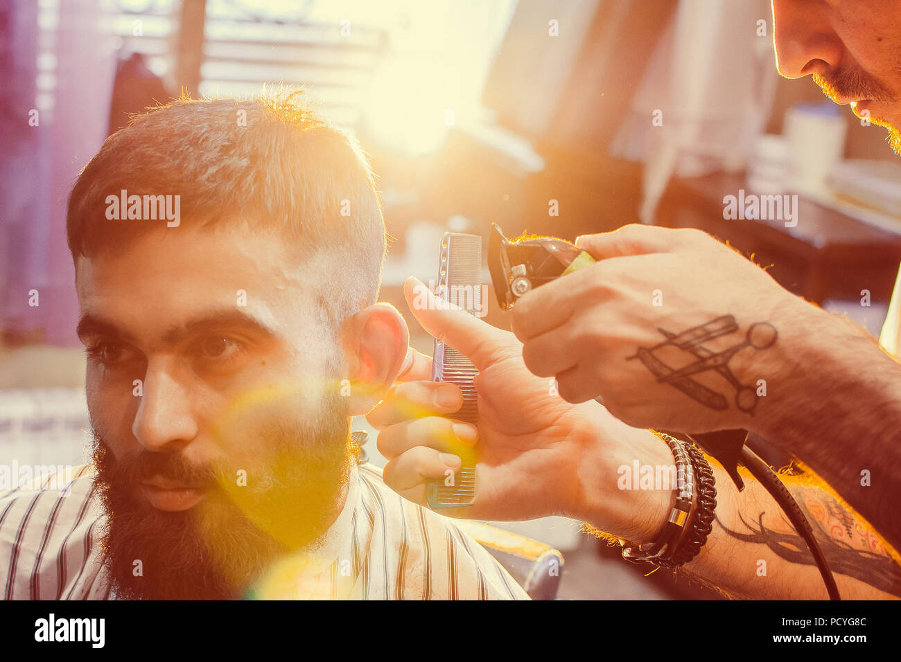 Barber does a haircut on his head with a trimmer to a young handsome guy with a mustache and beard. Men's hair salon. Stock Photo