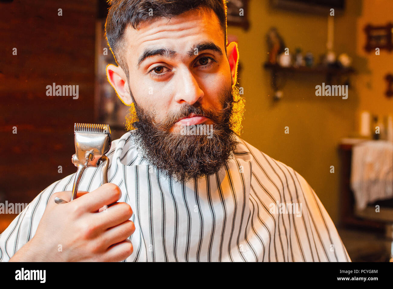 A young handsome guy with a beard and mustache is holding vintage hair clips in his right hand. Men's hair salon. - Stock Image