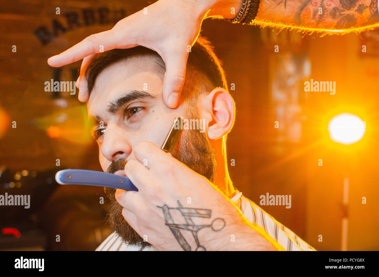 Barber shaves the dangerous razor of a handsome young man with a mustache and beard. Shaving a dangerous razor in a male hairdresser - Stock Image