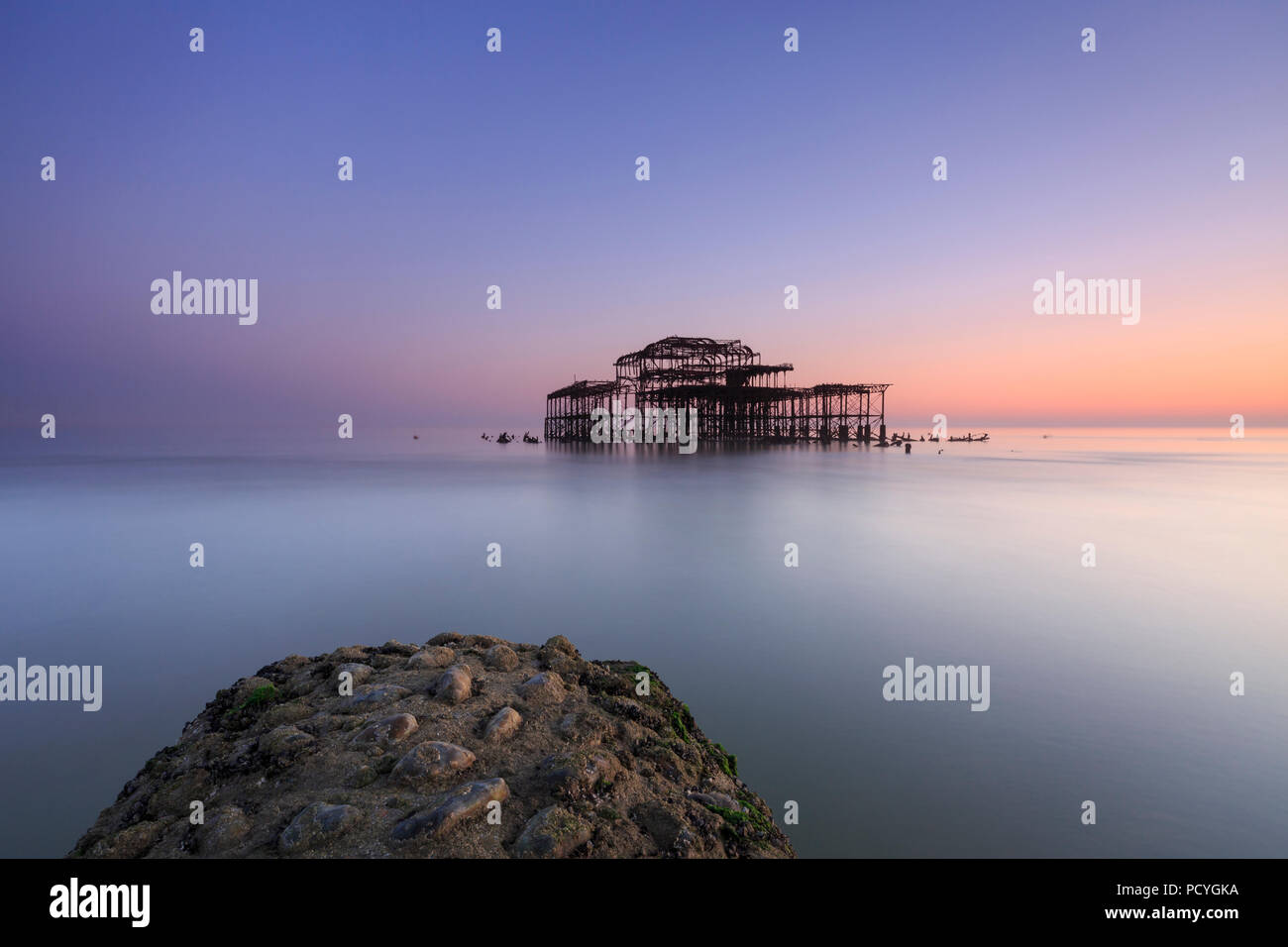 The ruins of the West Pier in Brighton at sunset and a low spring tide - Stock Image