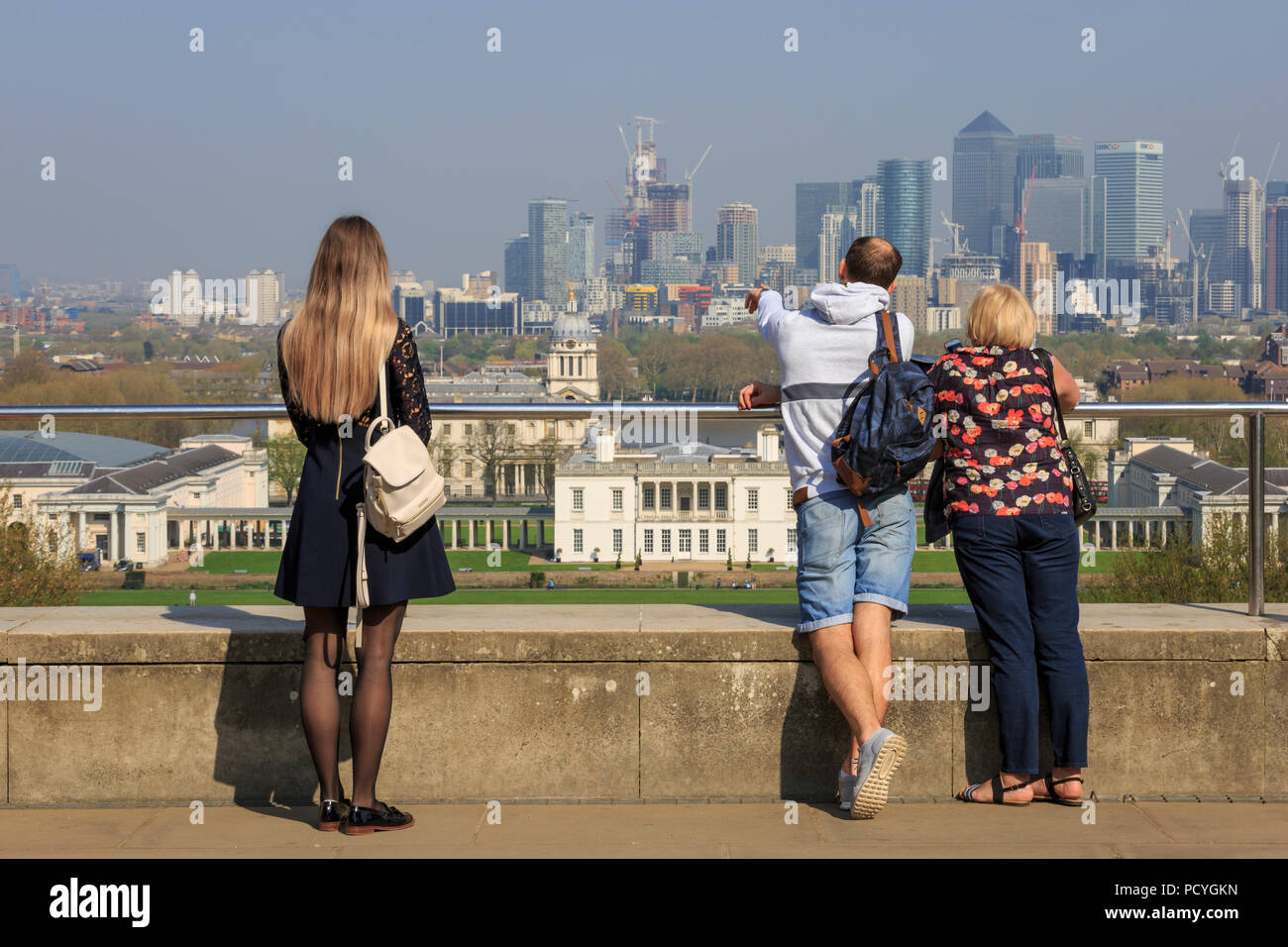 People look over towards the Docklands cityscape from the viewpoint, adjacent to the Royal Observatory, in Greenwich Park, on a bright sunny day - Stock Image
