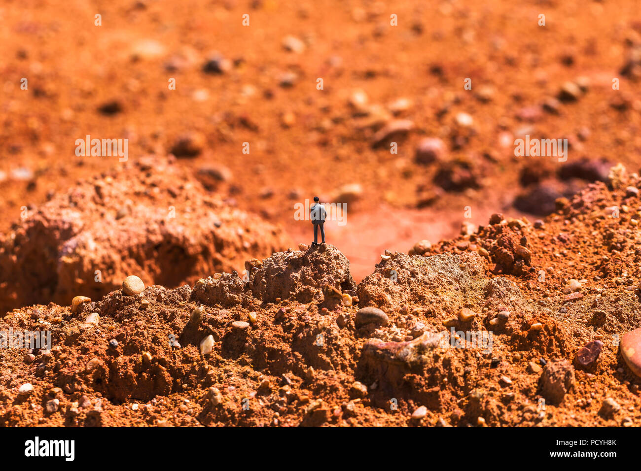 Business man on the rocky area is rocky. Imagine doing business on Mars. - Stock Image