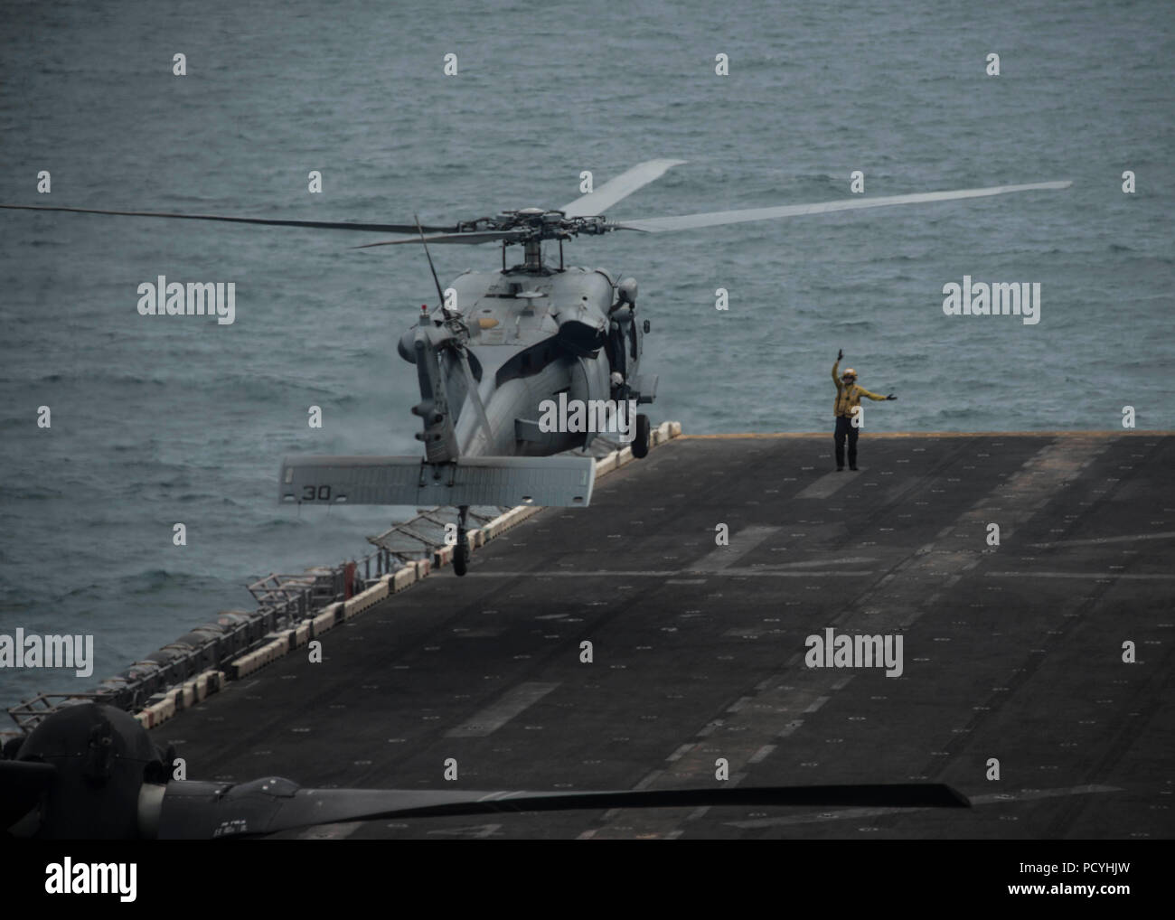 ATLANTIC OCEAN (Aug. 3, 2018) An MH-60S Sea Hawk, attached to Helicopter Sea Combat Squadron (HSC) 28, prepares to land on the flight deck of the Wasp-class amphibious assault ship USS Iwo Jima (LHD 7), Aug. 3, 2018. Iwo Jima is deployed with its amphibious ready group in support of maritime security operations and theatre security cooperation efforts in Europe and the Middle East. (U.S. Navy photo by Mass Communication Specialist 3rd Class Dominick A. Cremeans/Released) Stock Photo