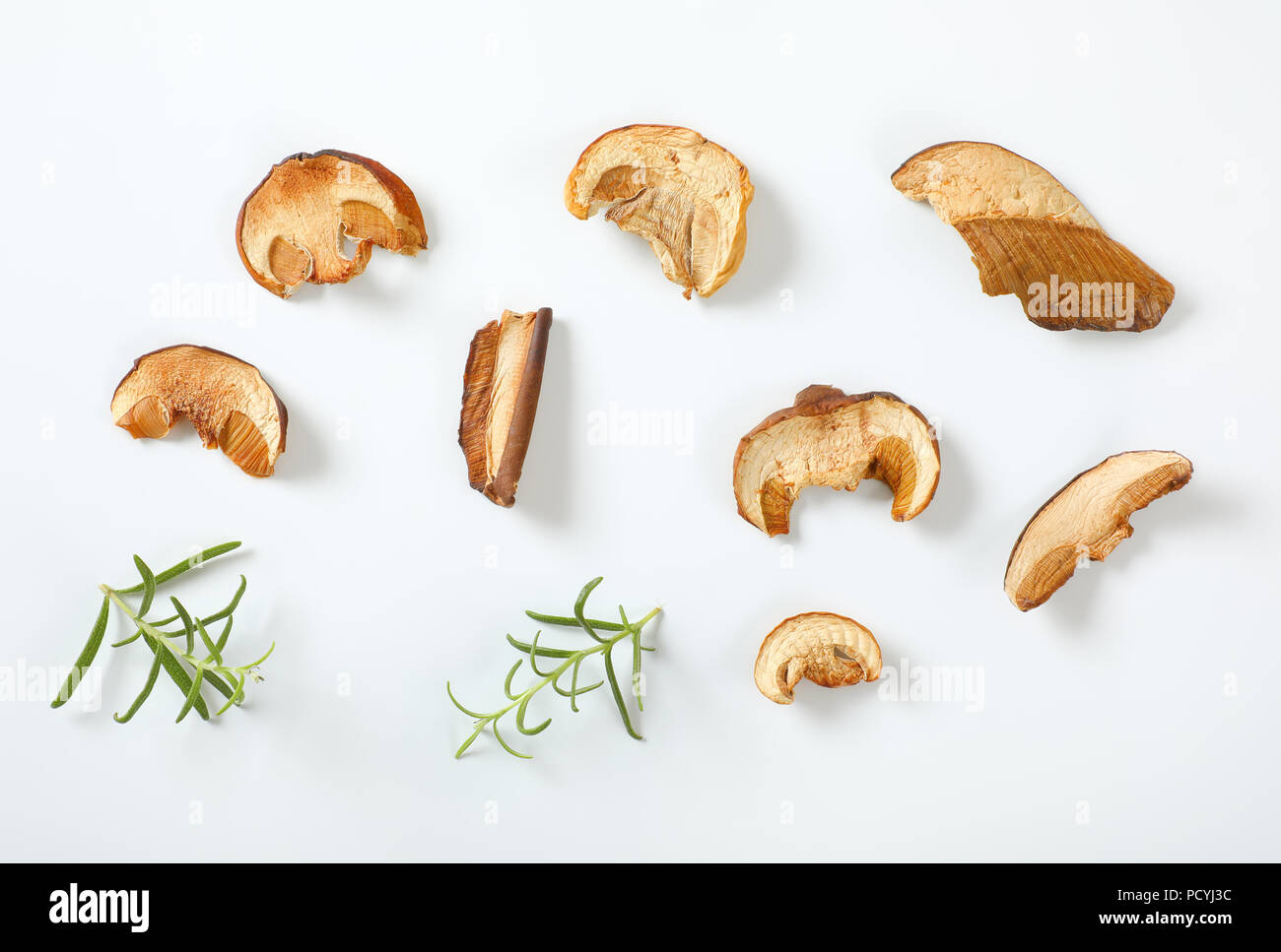 slices of dried mushrooms and rosemary on white background - Stock Image