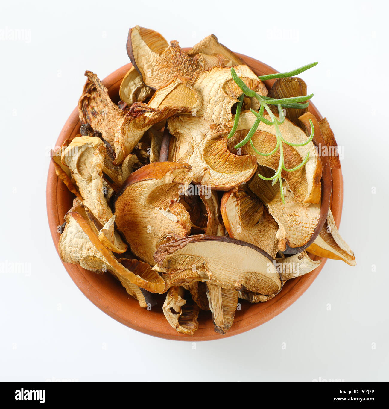 bowl of dried mushrooms on white background - Stock Image