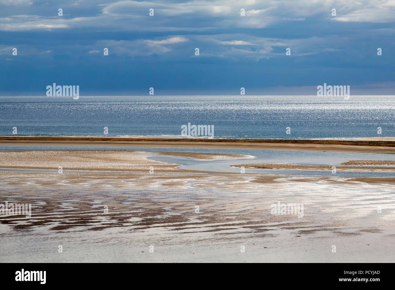 Sunlight sparkling on the sea and sand ripples at Red Sands