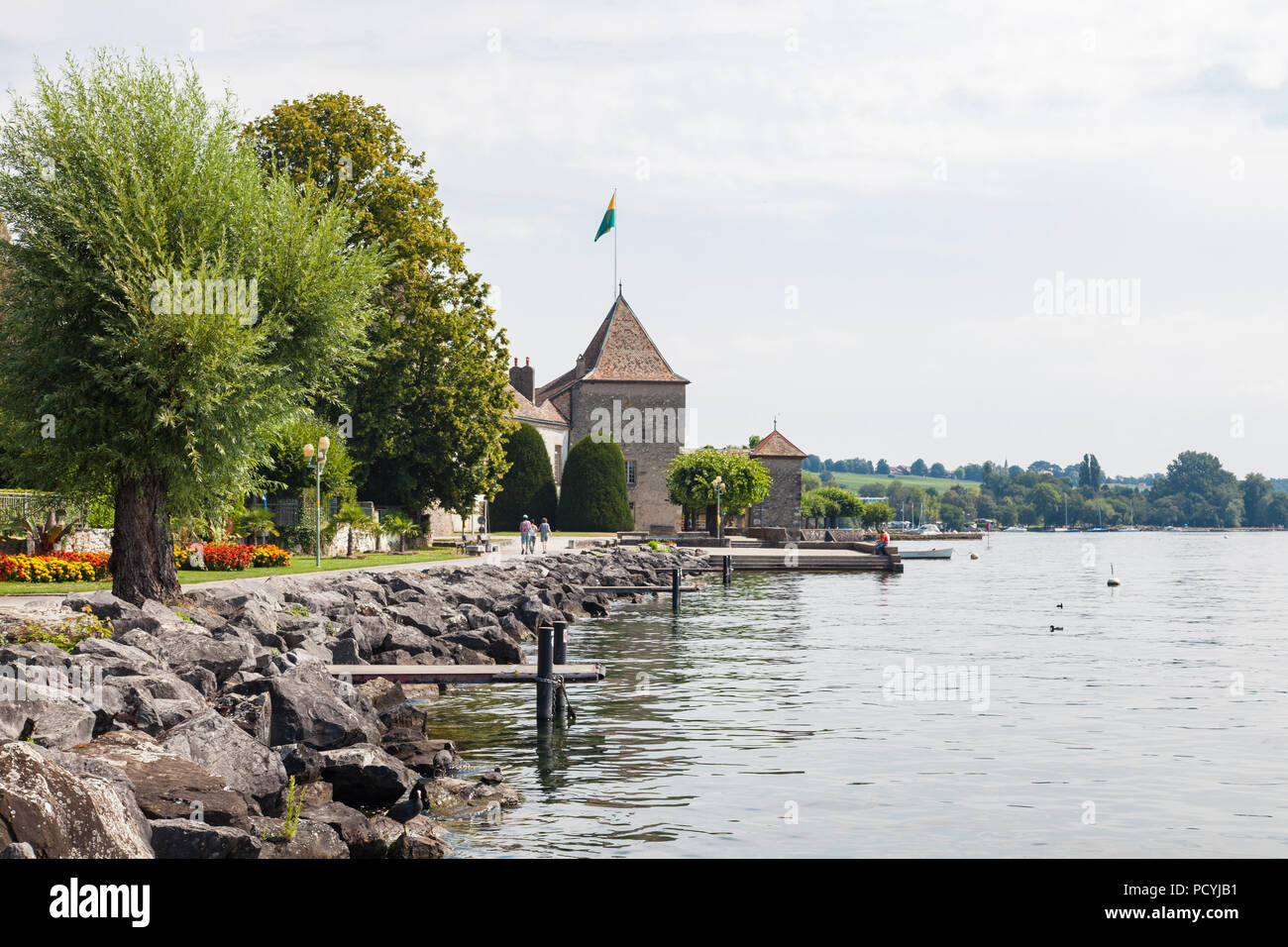 Beautiful promenade along Lake Leman (Geneva lake) waterfront, Rolle Castle and gardens in Rolle, La Côte Region, Vaud, Switzerland on hot summer day - Stock Image