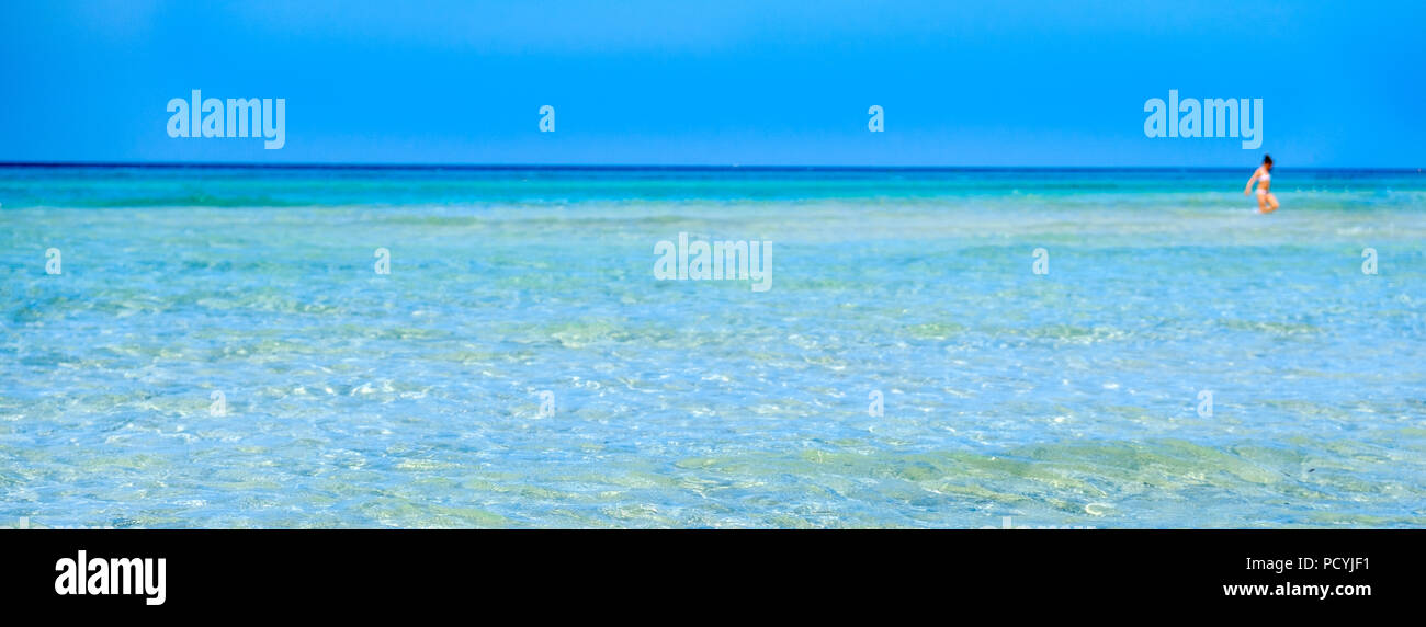 transparent water horizontal blur background crystalline sea girl walk saltwater flats - Stock Image