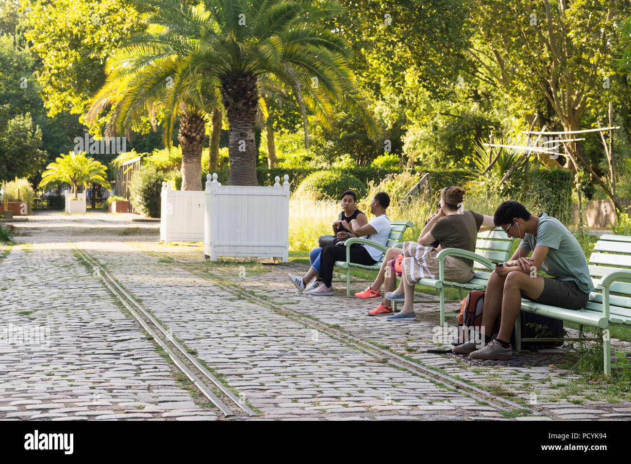 Paris park - People sitting on benches in the Park Bercy in the 13th arrondissement of Paris, France. Stock Photo