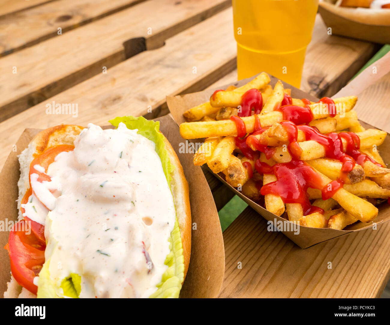 Takeaway food of lobster roll with chips or french fries with ketchup and half pint of lager on outdoor picnic table - Stock Image