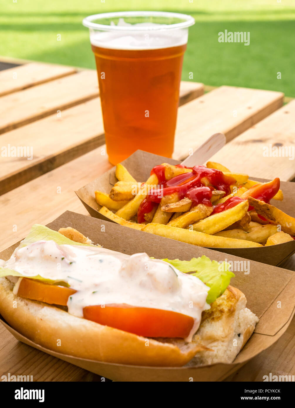 Takeaway food of lobster roll with chips or french fries with ketchup and pint of IPA beer on outdoor picnic table - Stock Image