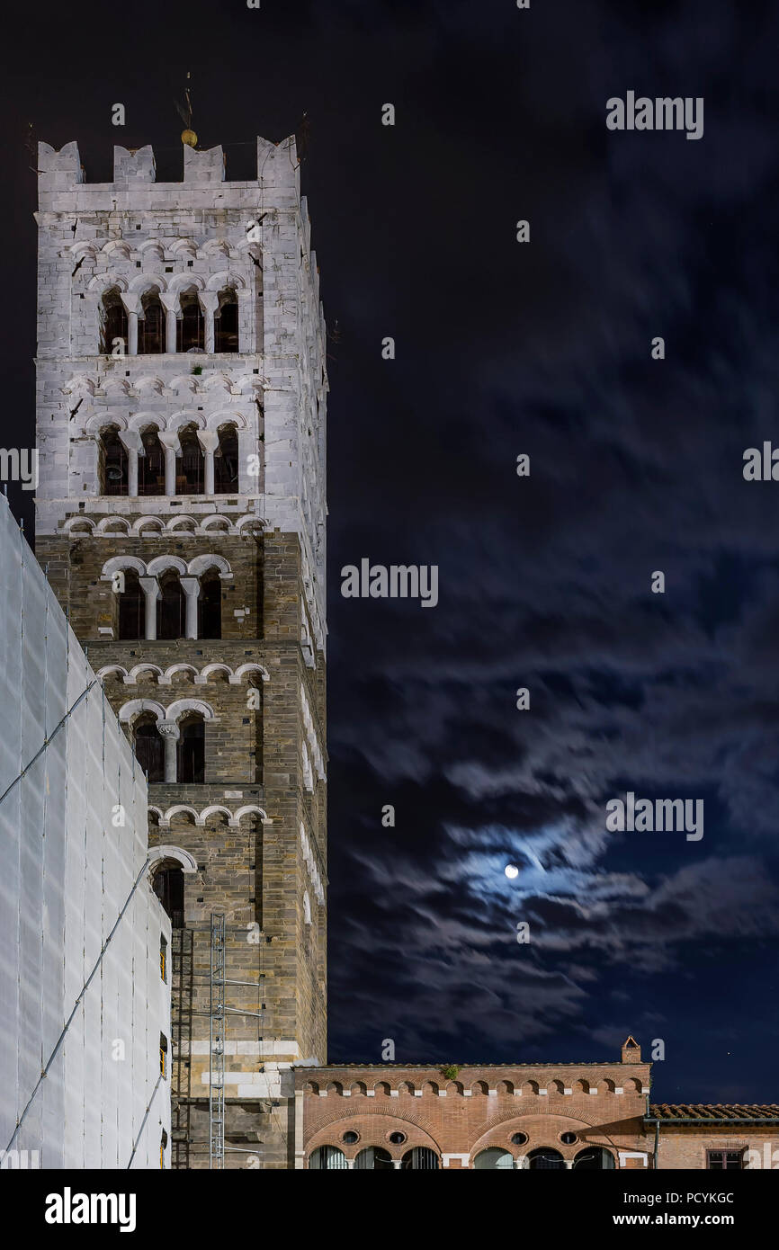 Beautiful view of the bell tower of the Duomo of San Martino with the moon and clouds in the night sky, Lucca, Tuscany, Italy Stock Photo