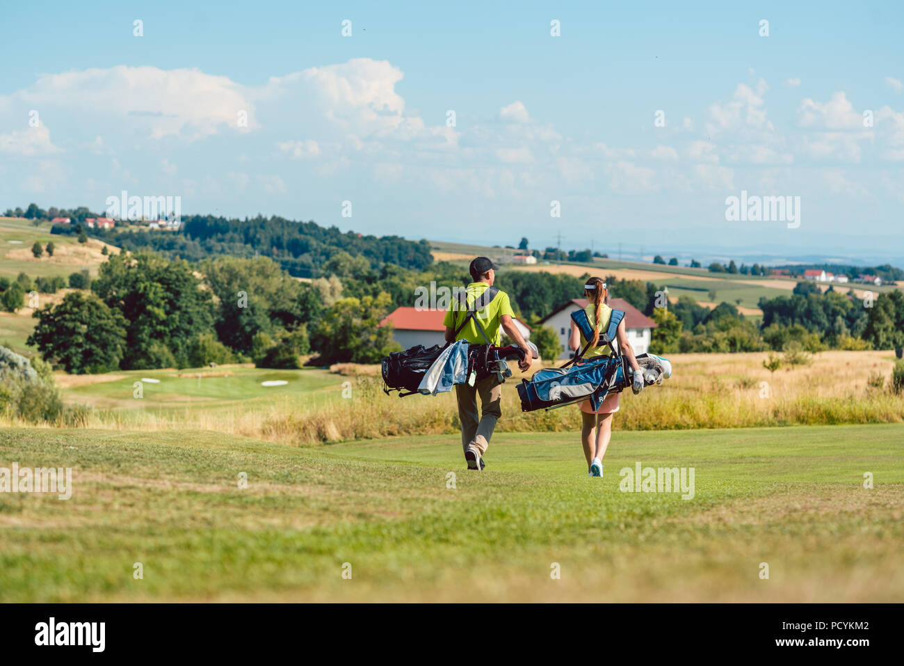 Full length rear view of a couple carrying golf bags - Stock Image