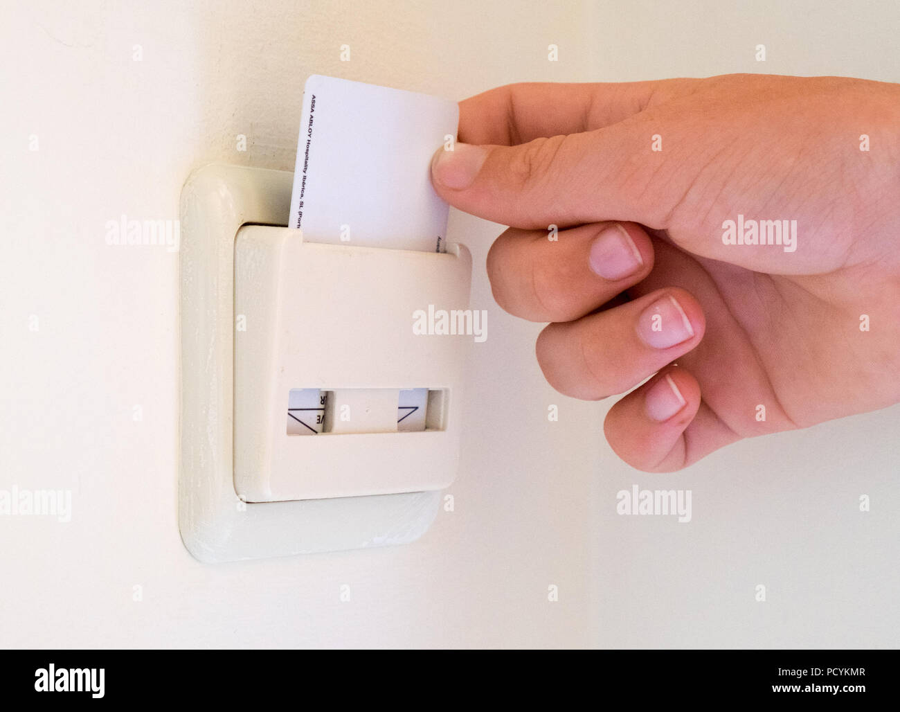 Hotel key card placed into a room switch to turn on the power - Stock Image