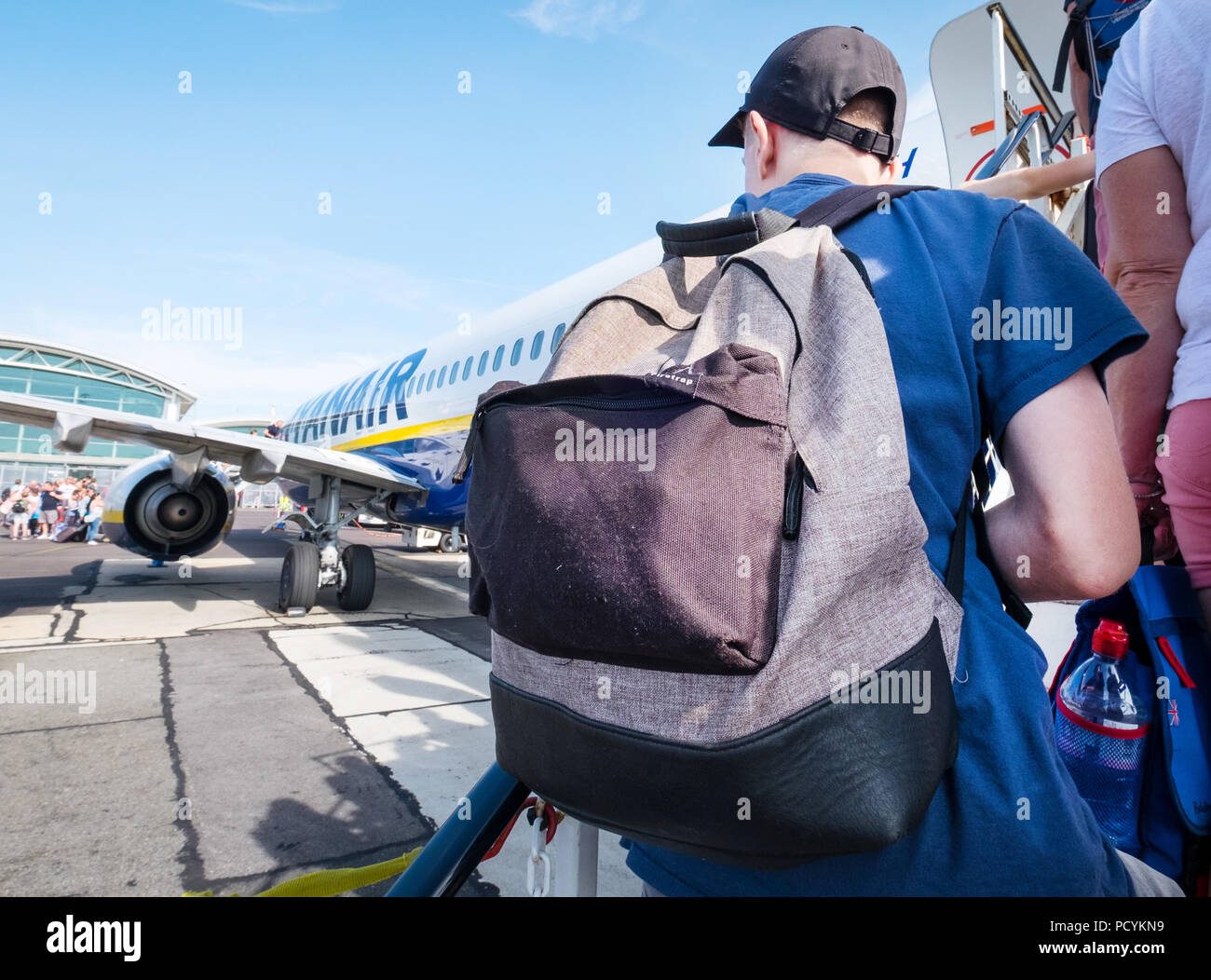 Ryanair passenger with a backpack as carry on hand luggage boarding a Ryanair plane after paying extra for priority boarding. - Stock Image