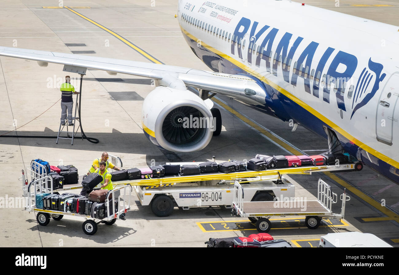 Baggage handlers loading bags into the hold of a Ryanair Plane at Faro Airport in Portugal - Stock Image