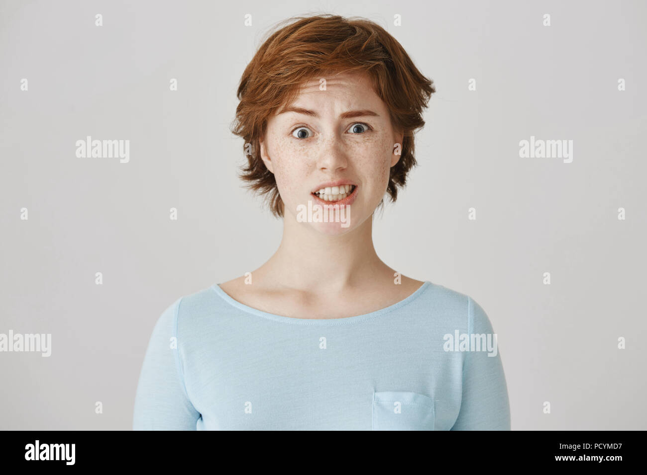 I am not sure it is good idea. Portrait of good-looking slender redhead woman with freckles grimacing and expressing hesitation and unwillingness to d - Stock Image