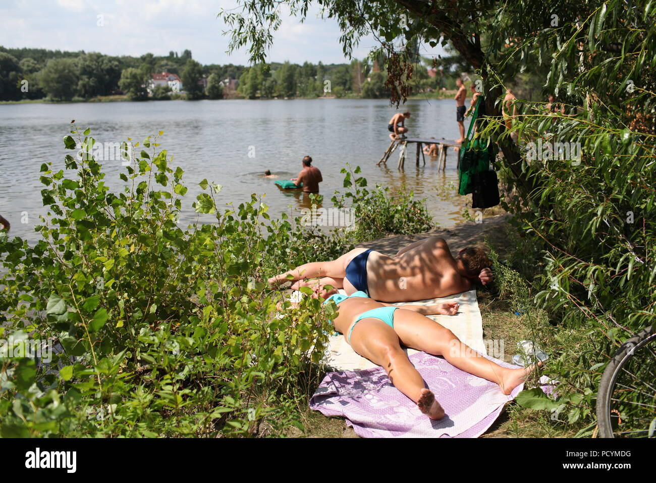 Young Ukrainian woman and man rest on bank of lake in Kiev enjoying delightful summer weather sunbath while other folks on beach fish and have fun - Stock Image