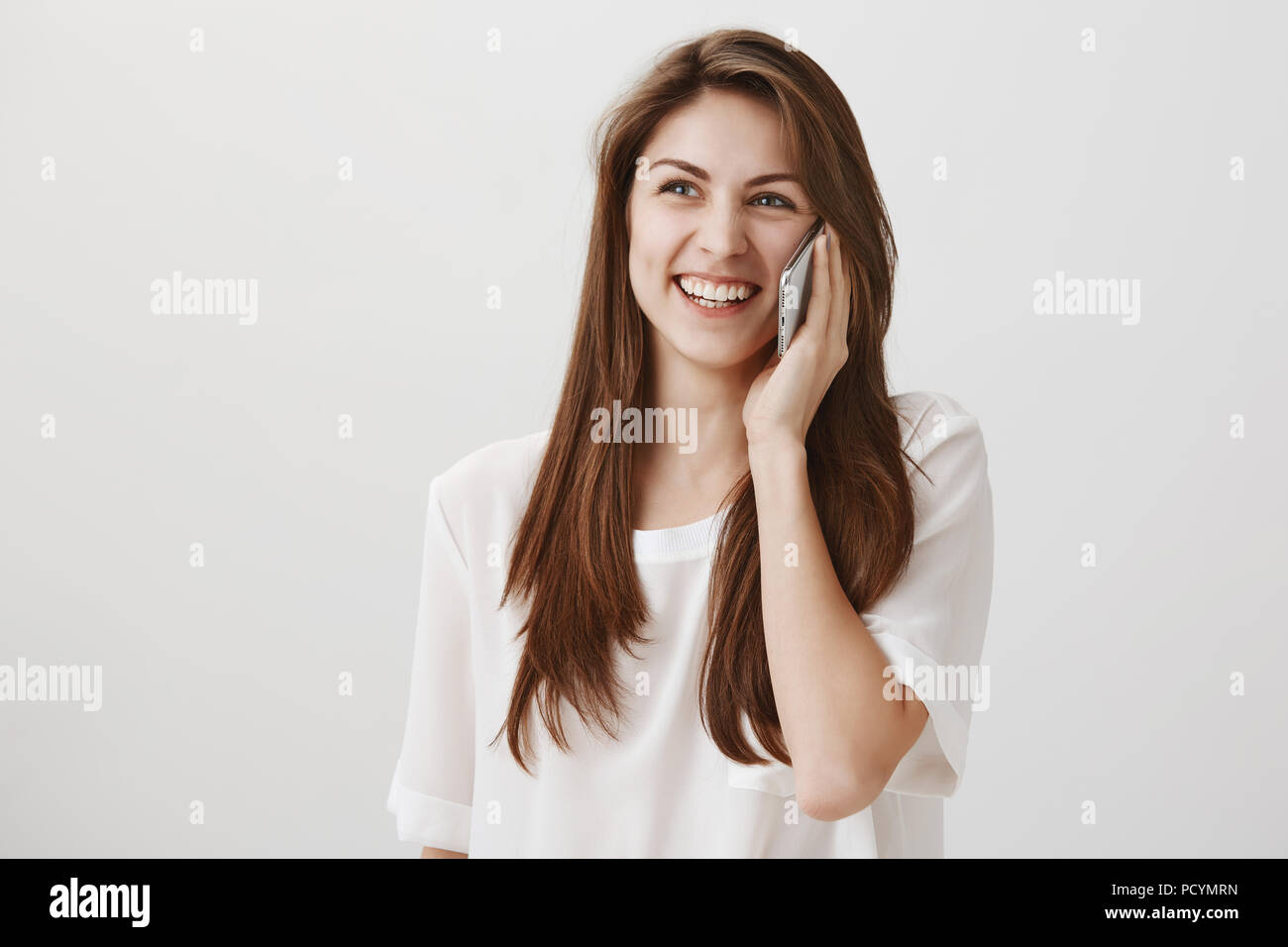 Her you loud and clear. Portrait of positive attractive female student laughing out loud and smiling broadly while talking on smartphone and looking u - Stock Image