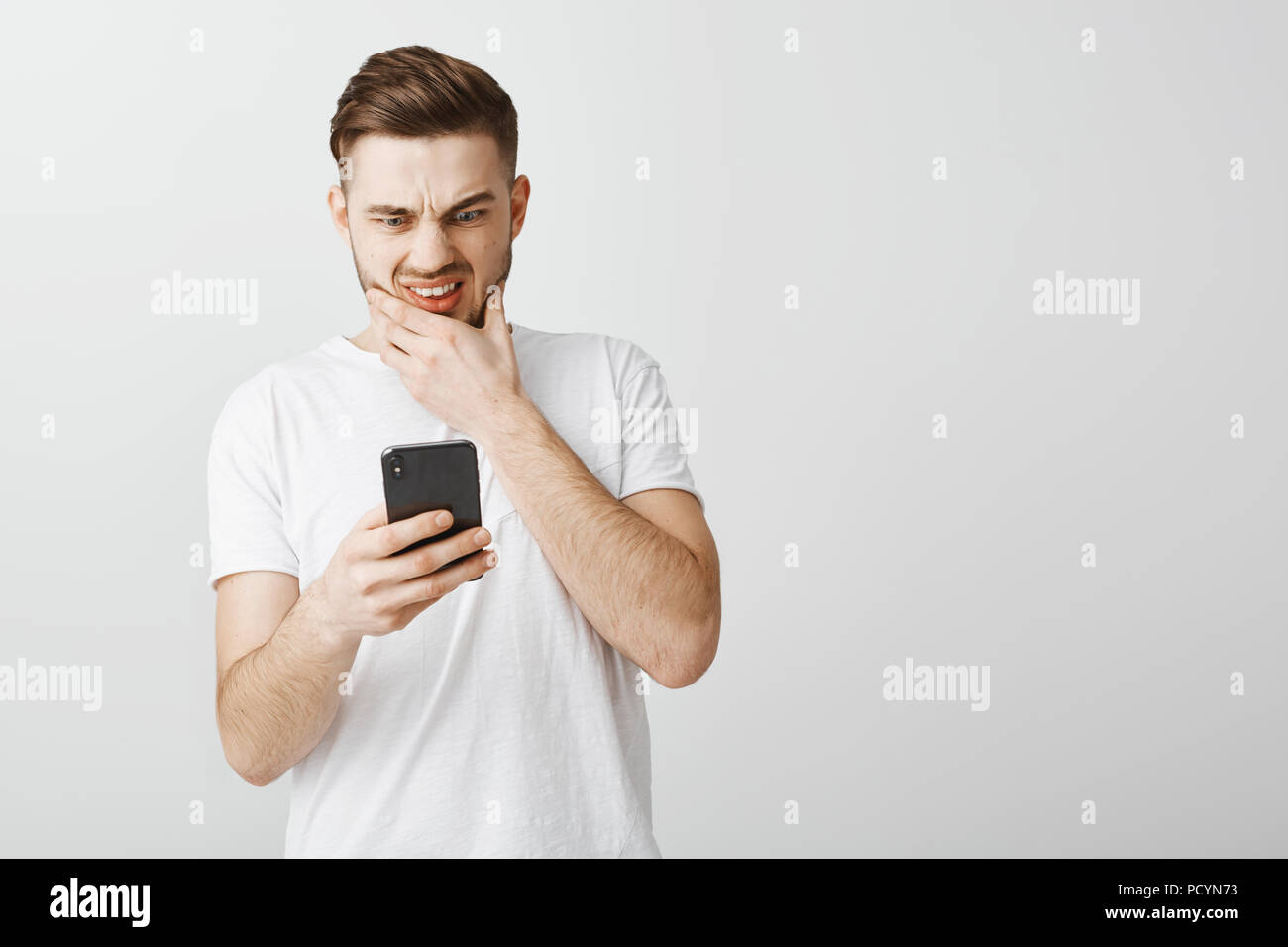 Guy send message to wrong person feeling anxious and concerned rubbing beard frowning and grimacing with opened mouth staring shook, worried at smartp - Stock Image