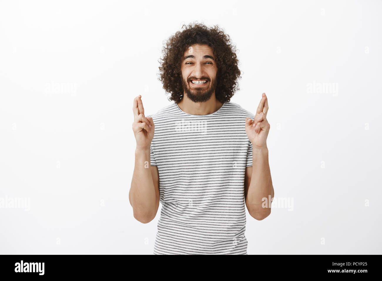 Indoor shot of anxious believing eastern bearded man with afro hairstyle, raising crossed fingers and grimacing from nervousness, wanting make wish co - Stock Image