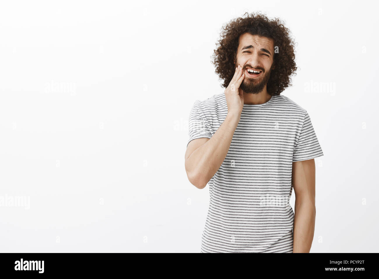 Portrait of displeased bothered handsome Eastern male student with afro hairstyle in striped t-shirt, touching beard and grimacing from dislike, feeli - Stock Image
