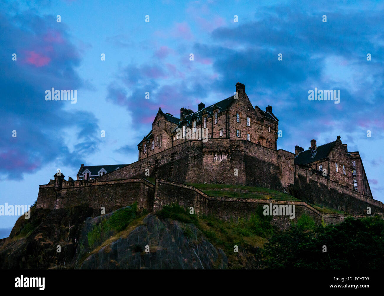 Edinburgh Castle rock at dusk sunset with dark blue sky and pink clouds, Edinburgh, Scotland, UK - Stock Image