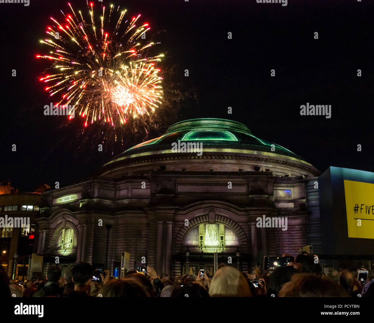 Fireworks over Usher Hall from Edinburgh Military Tattoo as crowd waits for opening event of EIF, Five Telegrams, Edinburgh, Scotland, UK Stock Photo